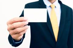 Uomo d'affari che tiene e che mostra l'isolato in bianco del biglietto da visita su fondo bianco Immagini Stock