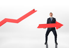 Uomo d'affari che tiene grande freccia rotta con entrambe le mani su fondo bianco Fotografia Stock