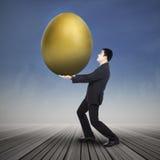 Uomo d'affari che tiene grande uovo dorato Fotografia Stock