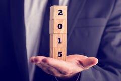 Uomo d'affari che tiene i blocchetti di legno del nuovo anno Fotografie Stock