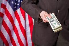 Uomo d'affari che tiene i dollari accanto alla bandiera fotografia stock
