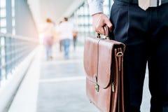 Uomo d'affari che tiene i viaggiatori di una cartella che camminano all'aperto Immagini Stock