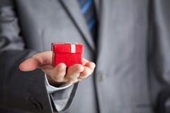 Uomo d'affari che tiene il contenitore di regalo rosso Fotografie Stock