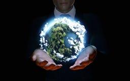 Uomo d'affari che tiene il mondo nella palma delle mani Fotografia Stock Libera da Diritti