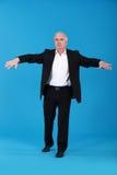 Uomo d'affari che tiene il suo equilibrio Fotografia Stock