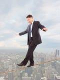 Uomo d'affari che tiene il suo equilibrio Immagine Stock