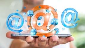 Uomo d'affari che tiene l'icona del email della rappresentazione 3D sopra il telefono cellulare Fotografia Stock