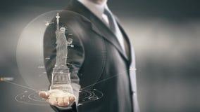 Uomo d'affari che tiene la statua disponibila del punto di riferimento delle tecnologie di Liberty New Immagini Stock