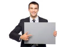 Uomo d'affari che tiene manifesto in bianco immagini stock