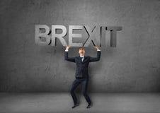 Uomo d'affari che tiene parola pesante 'del brexit 3d' sopra la sua testa Fotografie Stock