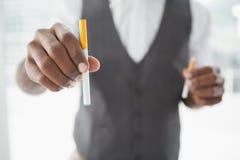 Uomo d'affari che tiene sigaretta elettronica e sigaretta Fotografia Stock Libera da Diritti