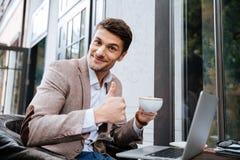 Uomo d'affari che tiene tazza di caffè e che lavora con il computer portatile all'aperto fotografie stock libere da diritti