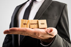 Uomo d'affari che tiene tre cubi di legno con le parole - noi respe Fotografia Stock Libera da Diritti
