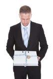 Uomo d'affari che tiene un archivio top-secret Immagine Stock