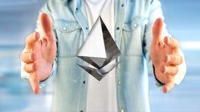 Uomo d'affari che tiene un aroun cripto di volo del segno di valuta di Ethereum Immagini Stock
