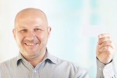 Uomo d'affari che tiene un biglietto da visita in bianco Fotografie Stock Libere da Diritti