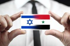 Uomo d'affari che tiene un biglietto da visita con Israele e la bandiera della Siria Immagini Stock