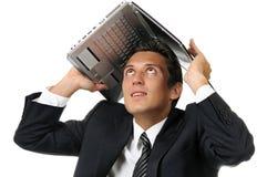 Uomo d'affari che tiene un computer portatile sopra la sua testa fotografie stock
