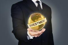 Uomo d'affari che tiene un globo dorato con l'investimento Immagini Stock