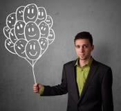 Uomo d'affari che tiene un mazzo di palloni sorridenti Fotografia Stock Libera da Diritti