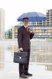 Uomo d'affari che tiene un ombrello Fotografie Stock Libere da Diritti