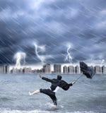 Uomo d'affari che tiene un ombrello con thundershower immagine stock