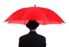 Uomo d'affari che tiene un ombrello rosso Fotografia Stock Libera da Diritti