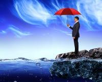 Uomo d'affari che tiene un ombrello rosso Fotografie Stock