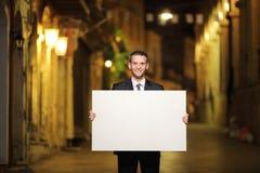 Uomo d'affari che tiene un pannello in una via della città fotografie stock libere da diritti