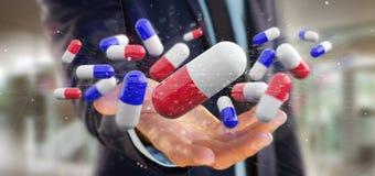 Uomo d'affari che tiene un 3d che rende gruppo di pillole mediche Fotografia Stock Libera da Diritti
