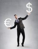 Uomo d'affari che tiene un simbolo dell'euro e del dollaro Fotografia Stock Libera da Diritti
