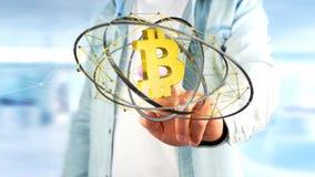 Uomo d'affari che tiene un volo cripto del segno di valuta di Bitcoin intorno Immagini Stock