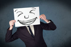 Uomo d'affari che tiene una carta con il fronte sorridente davanti al suo hea Fotografie Stock