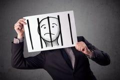 Uomo d'affari che tiene una carta con un prigioniero dietro le barre sopra i fotografia stock libera da diritti