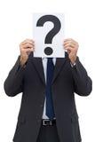 Uomo d'affari che tiene una carta del punto interrogativo Fotografia Stock
