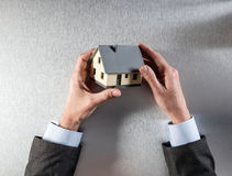 Uomo d'affari che tiene una casa per la valutazione o la vendita domestica della proprietà Immagini Stock Libere da Diritti