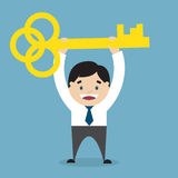 Uomo d'affari che tiene una chiave dorata di successo Immagine Stock Libera da Diritti