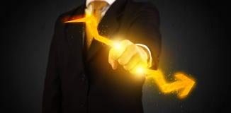 Uomo d'affari che tiene una freccia dritta d'ardore calda Immagine Stock