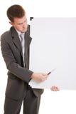 Uomo d'affari che tiene una scheda bianca. Fotografia Stock