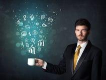 Uomo d'affari che tiene una tazza bianca con le icone di affari Fotografia Stock