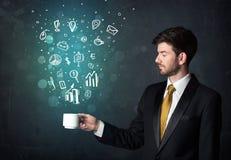 Uomo d'affari che tiene una tazza bianca con le icone di affari Fotografia Stock Libera da Diritti