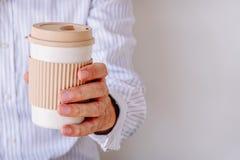 Uomo d'affari che tiene una tazza di caffè su un fondo bianco con lo spazio della copia immagine stock