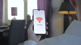Uomo d'affari che tiene uno smartphone che si collega al wifi stock footage
