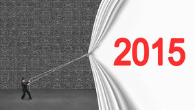 Uomo d'affari che tira giù tenda 2015 che copre vecchio wa grigio del mattone Immagini Stock Libere da Diritti