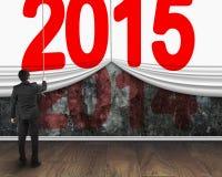 Uomo d'affari che tira giù tenda 2015 per riguardare vecchio buio 2014 Immagine Stock