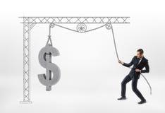 Uomo d'affari che tira il grande simbolo di dollaro del calcestruzzo 3d con la puleggia tirata isolata su fondo bianco Fotografie Stock Libere da Diritti