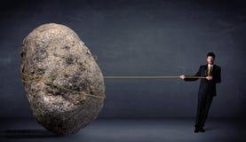 Uomo d'affari che tira roccia enorme con una corda Fotografia Stock Libera da Diritti