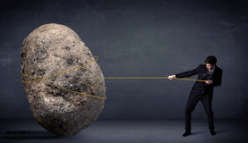 Uomo d'affari che tira roccia enorme con una corda Immagine Stock