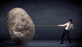 Uomo d'affari che tira roccia enorme con una corda Immagini Stock Libere da Diritti