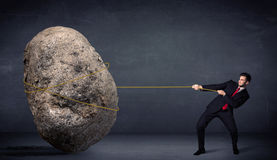 Uomo d'affari che tira roccia enorme con una corda fotografie stock libere da diritti